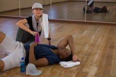 Danseur masculin fatigué dormant par la femme dans le studio Photo stock