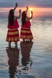 Danseurs de danse polynésienne dans l'océan au coucher du soleil Photos stock