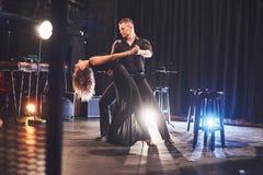 Danseurs habiles exécutant dans la chambre noire sous la lumière photo libre de droits