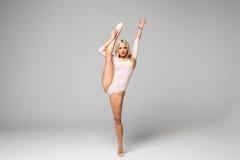 Danseuse de femme avec la jambe, s'étirant sur le fond blanc Image stock
