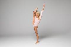 Danseuse de femme avec la jambe, s'étirant sur le fond blanc Photos stock