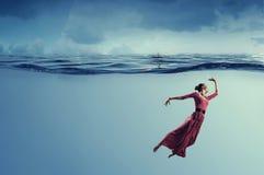 Danseuse de femme dans l'eau bleue claire Photographie stock