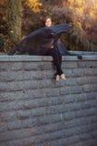Danseuse de fille avec le châle noir s'asseyant sur un mur en pierre Photographie stock