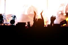 Dansflicka på skuldror i folkmassan på en musikfestival arkivfoto