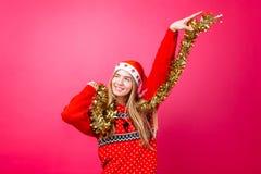 Dansflickan i röd tröja och jultomtenhatten, har gyckel med glitter på halsen som firar nytt år på röd bakgrund arkivbild