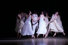 Dansflygkvinnan i vita klänningar hoppar upp royaltyfria bilder