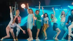 Dansgolv Många attraktiva kvinnor dansar på golvet lyftte upp händer, arkivfilmer