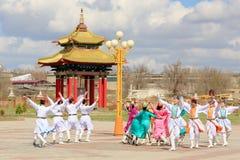 Dansgruppen av Kalmyk nationella dräkter dansar på bakgrunden royaltyfri bild