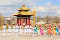 Dansgruppen av Kalmyk nationella dräkter dansar på bakgrunden royaltyfri foto