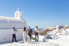 dansing在圣托里尼海岛,希腊上的婚礼的新娘和新郎 库存照片