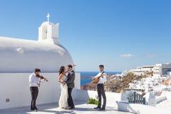 dansing在圣托里尼海岛,希腊上的婚礼的新娘和新郎 图库摄影
