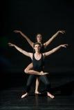 dansing在黑背景的年轻跳芭蕾舞者 免版税库存图片