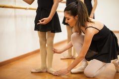 Dansinstructeur die meisjes met houding helpen stock foto