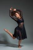 Danskvinna i en svart klänning Modern modern dans på en grå bakgrund Arkivfoto