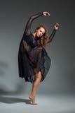 Danskvinna i en svart klänning Modern modern dans på en grå bakgrund Royaltyfri Fotografi