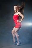Danskvinna i röd klänning på svart bakgrund Fotografering för Bildbyråer