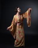 Danskvinna i traditionell japansk kimono på svart bakgrund Royaltyfri Fotografi