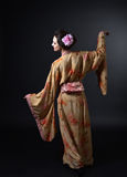 Danskvinna i traditionell japansk kimono på svart bakgrund Arkivfoto