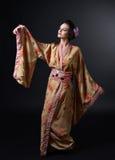 Danskvinna i traditionell japansk kimono på svart bakgrund Arkivbild