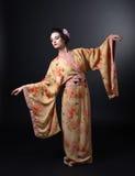 Danskvinna i traditionell japansk kimono på svart bakgrund Fotografering för Bildbyråer