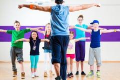 Danslärare som ger ungar Zumba konditiongrupp Arkivbild