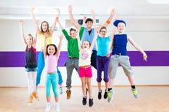 Dansleraar die de geschiktheidsklasse geven van jonge geitjeszumba Stock Foto's