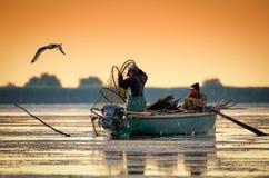 Danube Delta, Romania, June 2017: fishermans checking nests at s. Unrise in Danube Delta royalty free stock image