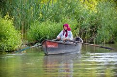 Danube delta - water city: old woman floating a boat Royalty Free Stock Image