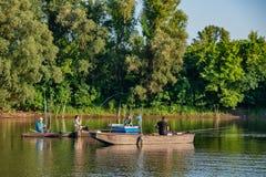 Danube island Šodroš near Novi Sad, Serbia. Fishermans sitting in boat and holding fishing r stock photos