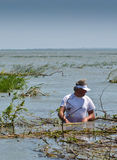 Danube river delta. Man clears the way for his boat Royalty Free Stock Images