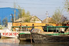 Danube river and fishing boat near the shore on a spring day. Channels along the streets like in Venice. Coast with reeds and water with a duckweed. Vilkovo stock photos