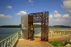 Danube riverside abstract door. Military style dressed tourist woman taking pictures under abstract door at Danube river shore at city of Silistra,Bulgaria Royalty Free Stock Photos