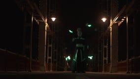 Danza con el poi llevado de los artistas hombre y mujer del circo en el puente vacío metrajes