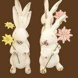 Danza del conejito de pascua cuatro pequeños conejos que sostienen las flores están en la formación que hace una danza de Pascua  foto de archivo libre de regalías