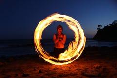 Danza del fuego a lo largo de la playa en la obscuridad foto de archivo