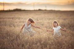 Danza emocional de dos muchachas de las hermanas en la puesta del sol foto de archivo