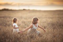 Danza emocional de dos muchachas de las hermanas en la puesta del sol imagen de archivo