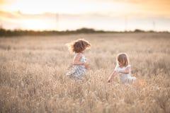 Danza emocional de dos muchachas de las hermanas en la puesta del sol imagenes de archivo