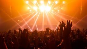 Danza feliz de la gente en concierto del partido del club nocturno Imagenes de archivo