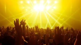 Danza feliz de la gente en concierto del partido del club nocturno imagen de archivo