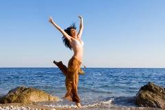 Danza feliz de la mujer en la playa Fotos de archivo libres de regalías