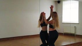 Danza femenina del entrenamiento del bailar?n mientras que ensaya en estudio de la danza metrajes