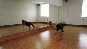 Danza femenina del entrenamiento del bailar?n mientras que ensaya en estudio de la danza almacen de metraje de vídeo