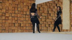 Danza flexible atractiva de la mujer delante del espejo en estudio metrajes