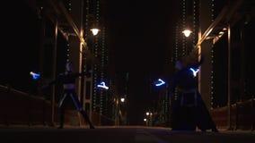 Danza hermosa con el poi llevado de los artistas hombre y mujer del circo en el puente vacío almacen de metraje de vídeo