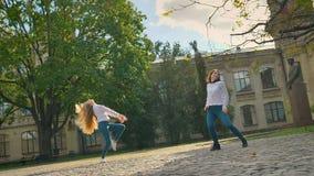 Danza libre de dos muchachas caucásicas hermosas, Sunny Day And SUnlights en el cuadrado, dando vuelta en círculo y bailarines de almacen de metraje de vídeo