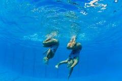 Danza subacuática sincronizada de las muchachas Foto de archivo