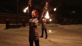 Danza tribal asombrosa de la demostración del fuego en la noche el invierno debajo de la nieve que cae El grupo de la danza se re almacen de video
