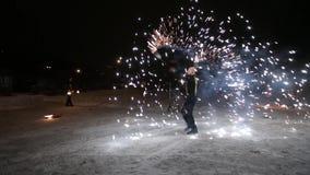 Danza tribal asombrosa de la demostración del fuego en la noche el invierno debajo de la nieve que cae El grupo de la danza se re metrajes