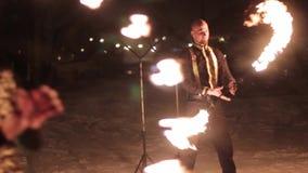 Danza tribal asombrosa de la demostración del fuego en la noche el invierno debajo de la nieve que cae El grupo de la danza se re almacen de metraje de vídeo